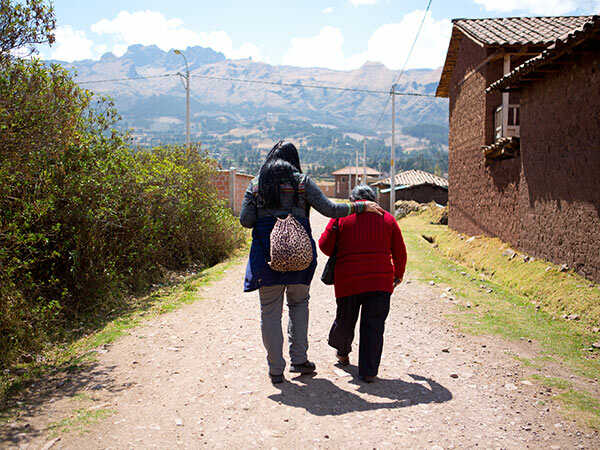 a missionary walks with an elderly woman in a village
